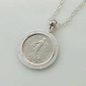 写真:大ぶりのコインで存在感のあるペンダントトップに。 シンプルなシルバーの枠に、クリアのジルコニアが8個石留